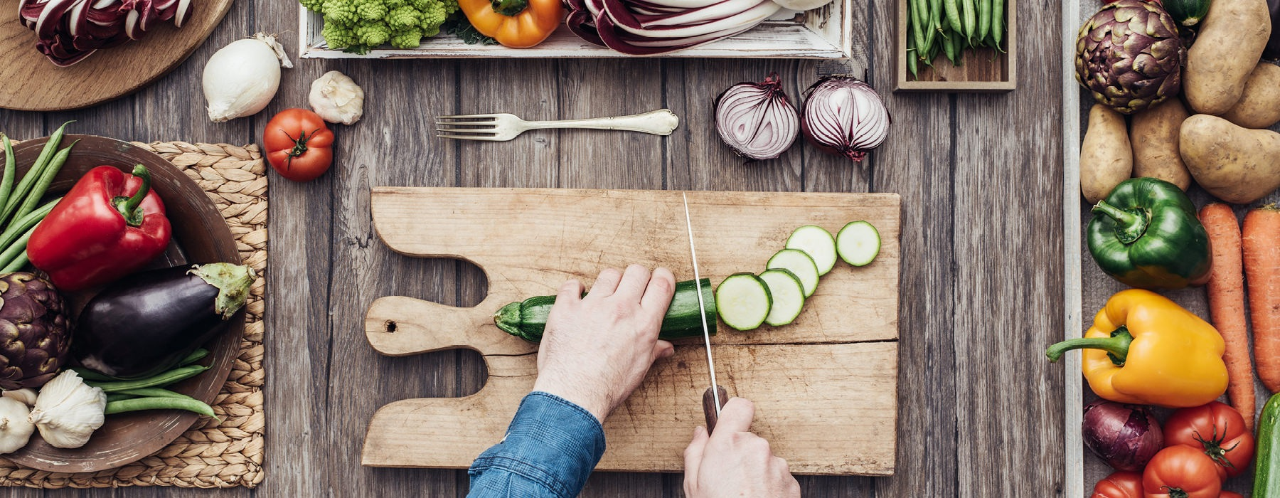man slicing zucchini on wooden cutting board surrounded by fresh vegetables on large wood table